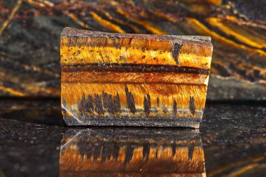 Close-up of natural mineral gem stone - Tiger's eye on dark polished slab opposite another tiger eye stones. Gemstone tiger eye with a golden color.